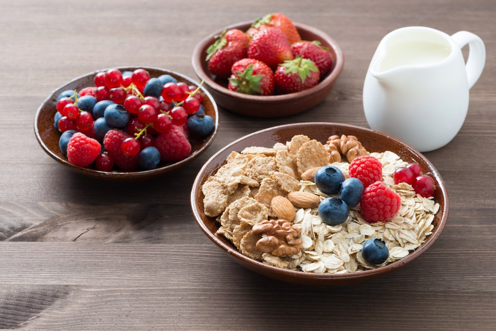 oatmeal and muesli in a bowl, fresh berries and milk on wooden table, horizontal